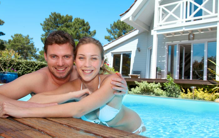 couple posing by edge of swimming poo