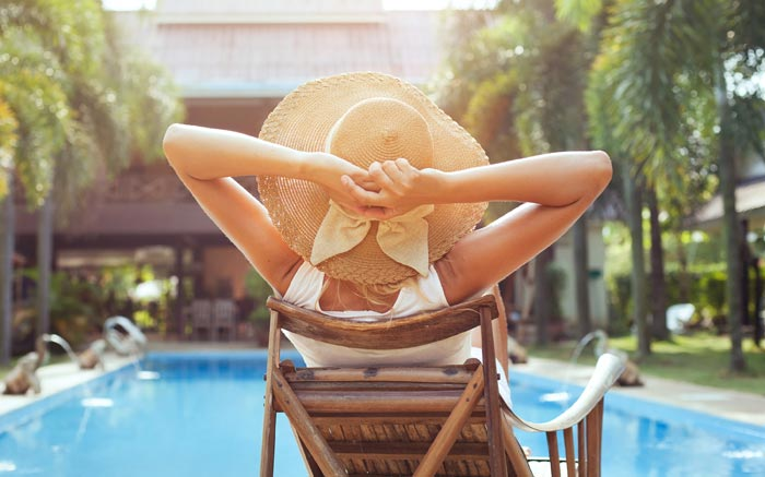 lady with shade hat relaxing in chair by pool