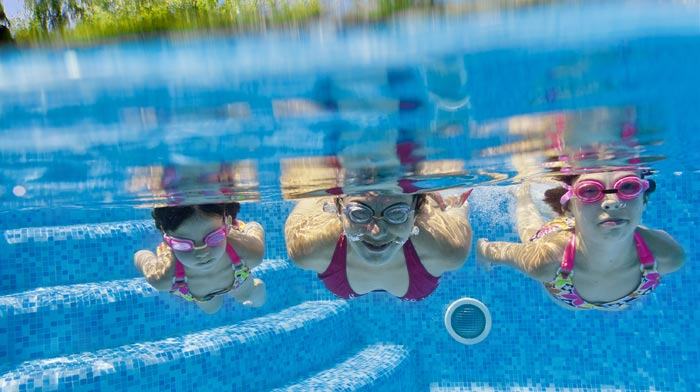 Mother and daughters with goggles swimming underwater